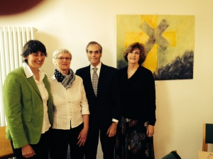 """(L to R) Pastorin Martina Dittkrist, artist Hannlore Golberg, me, and Vickie standing in front of Ms Golberg's painting of """"The Broken Cross"""" symbolizing the ongoing atonement of the community of the Michaeliskirche in Kaltenkirchen for the crimes of their one time Pastor Ernst Biberstein who was tried and convicted at Nuremberg of mass murder."""